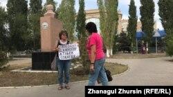 Гражданская активистка Алима Абдирова с плакатом в поддержку политзаключенных. Актобе, 8 августа 2019 года.