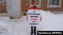 Эльнора Мирзаева в пикете на фоне своего дома