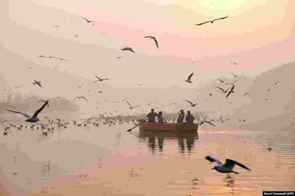 Indian women take pictures on a boat as migratory birds fly overhead on the Yamuna River on a morning of heavy air pollution in New Delhi. (AFP/Noemi Cassanelli)