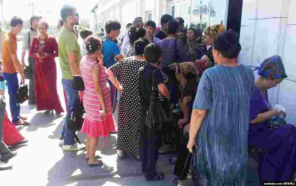 Türkmenabatdaky otly wokzalyndaky kassanyň öňünde adamlar bilet almaga synanyşýarlar.