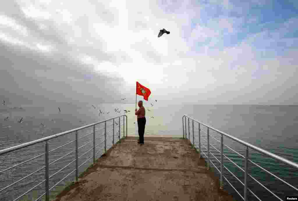 A man holds a Soviet flag as he stands on a pier during the opening of the cold-water swimming season in the Black Sea town of Saky, Crimea, on November 24. (Reuters/Pavel Rebrov)