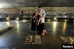 """Пожилая израильтянка оплакивает свою семью в Зале памяти комплекса """"Яд ва-Шем"""""""