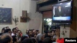 В кафе на каирской площади Тахрир демонстранты смотрят выступление президента Мохаммеда Мурси
