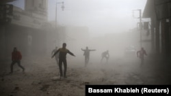 Civilians are seen running after an air raid in the besieged town of Douma in eastern Ghouta in Damascus on February 6.