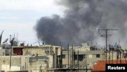 عمود من الدخان يتصاعد في مدينة حمص السورية إثر إضطرابات شهدتها في 13/1/2012.