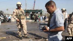 Iraqi police inspect a crater at the scene of the car bombing in Karbala.