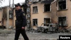 Сотрудник полиции у сгоревшего здания отеля, подожженного во время акции протеста. Исмаиллы, 25 января 2013 года.