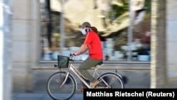 Велосипедист в маске на улице в германском Дрездене. 20 апреля 2020 года.