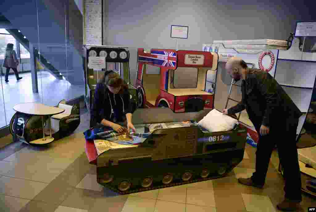 Anton Koppel, head of CaroBus furniture company, and an employee with a child's bed in the shape of a Buk missile launcher at the company's showroom in St. Petersburg. An international criminal investigation recently found that a Malaysia Airlines passenger jet was shot down by a Buk missile fired from separatist-controlled territory in Ukraine in 2014. Investigators found that the Buk was brought into Ukraine from Russia shortly before the tragedy and then smuggled back to Russia shortly afterward. (AFP/Olga Maltseva)