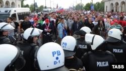 Полиция Ресей жанкүйерлерін жергілікті фанаттардан ажыратып алып тұр. Варшава, 12 маусым 2012 жыл