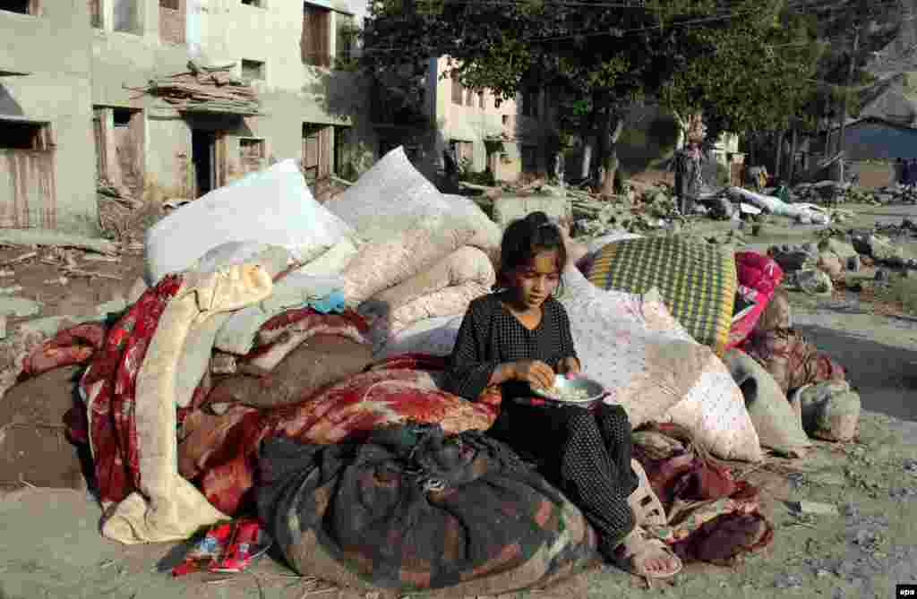 An Afghan girl affected by the floodwaters sits beside her belongings near damaged houses in the Sarobi district of Kabul.