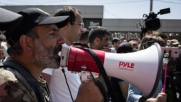 Armenian opposition leader Nikol Pashinian addresses supporters on the streets of Yerevan with a bullhorn on April 26.