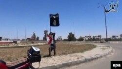 """""""Ислам мемлекеті"""" ұйымы содырының Рамади көшелерінің біріне ұйым туын тігіп жатқан сәті. Рамади, Ирак, 16 мамыр 2015 жыл."""