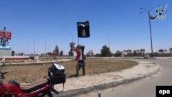 """Боевик """"Исламского государства"""" с флагом группировки на въезде в иракский город Рамади. Весна 2015 года"""