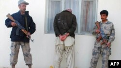 Afghan policemen guards an arrested drug smuggler in Herat.