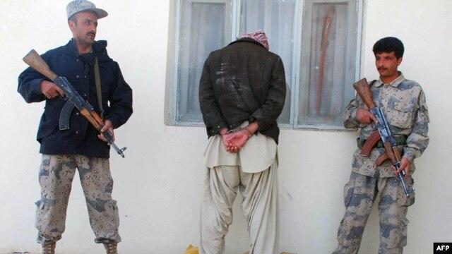 Afghan policemen guards an arrested drug smuggler in Herat.