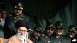 In front of Iranian Revolutionary Guards commanders, supreme leader Ayatollah Ali Khamenei, bottom left, attends a gathering of Basij paramilitary forces, in Tehran, Iran, Monday, Nov. 26, 2007.