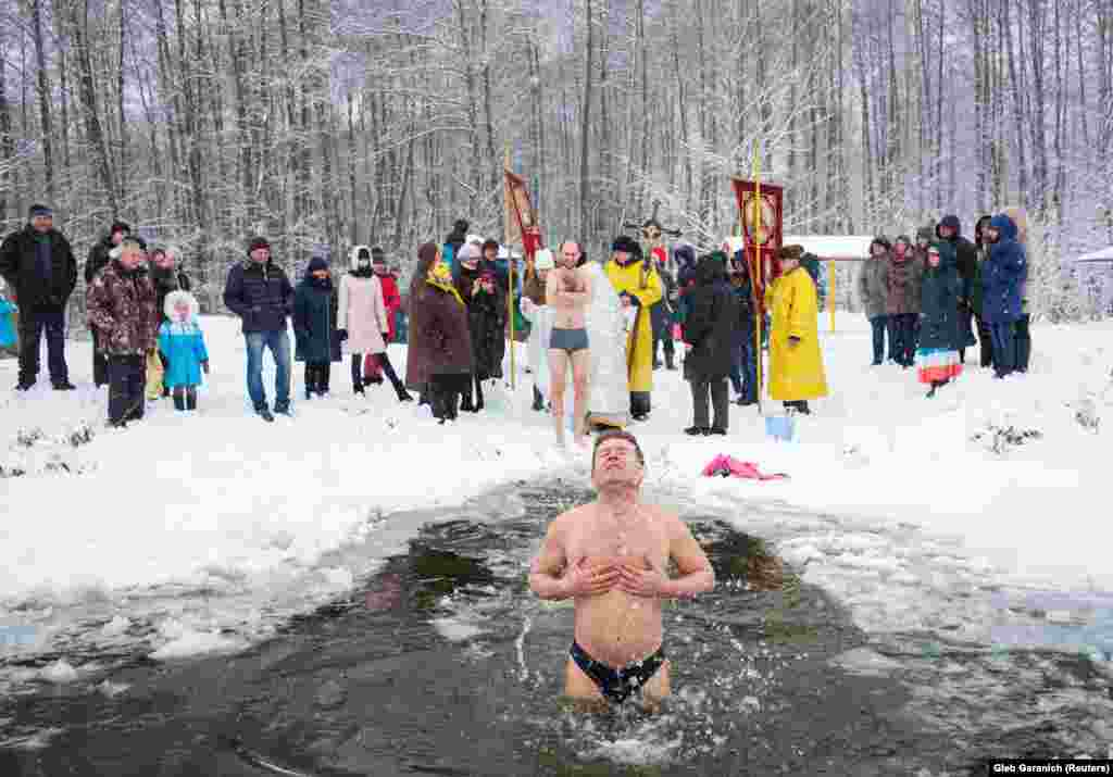 Locals of Ivankovichy plunging into icy water during a religious ceremony. The reforms to Ukraine's health-care system are scheduled to take place by 2020.
