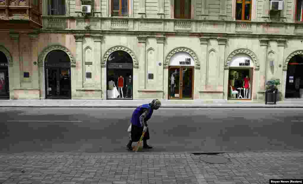 A woman sweeps a street in front of fashion boutiques in Baku.