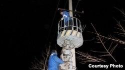 Электрики восстанавливают линии электропередач, оборванные шквальным ветром. Каратау, 12 января 2013 года. Фото из социальной сети Facebook.