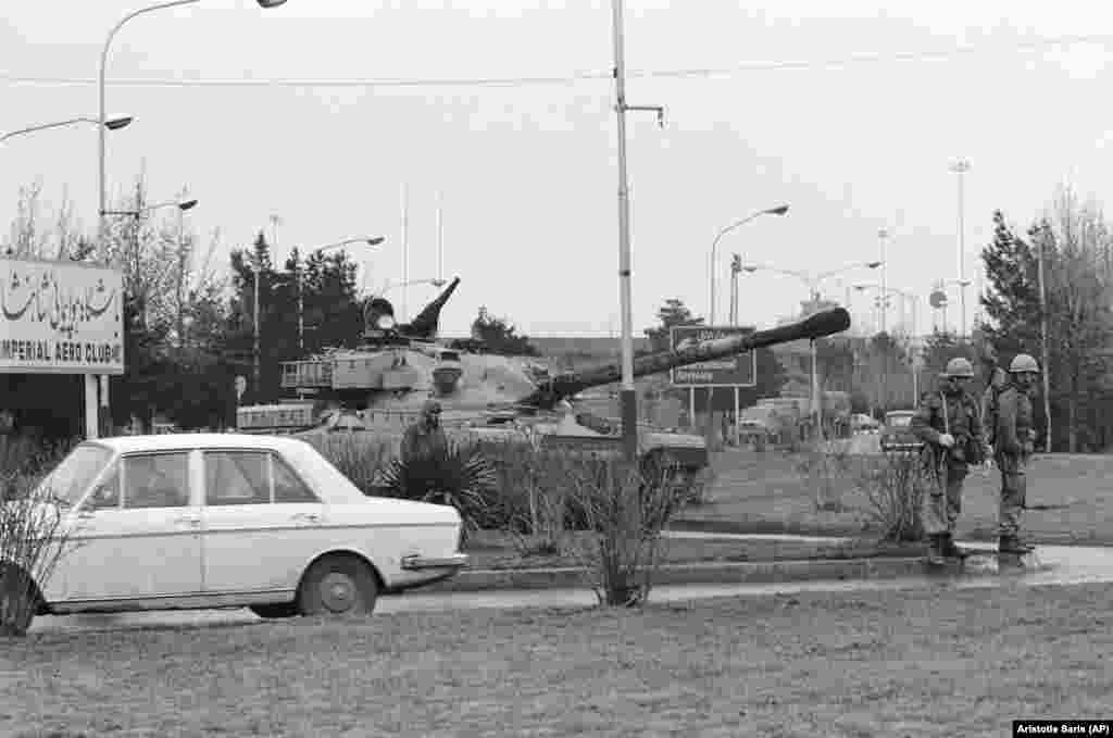An Iranian army tank and soldiers on a road leading to Tehran's airport. The army prevented an Iranian Airlines jet from taking off for Paris to pick up exiled Islamic leader Ayatollah Khomeini for his return to Iran.