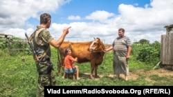 Архівне фото: український військовий розпитує мешканців Чермалика про наслідки обстрілу