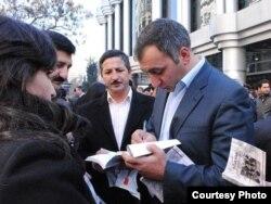 Şərif Ağayar oxucuları üçün kitabını imzalayır