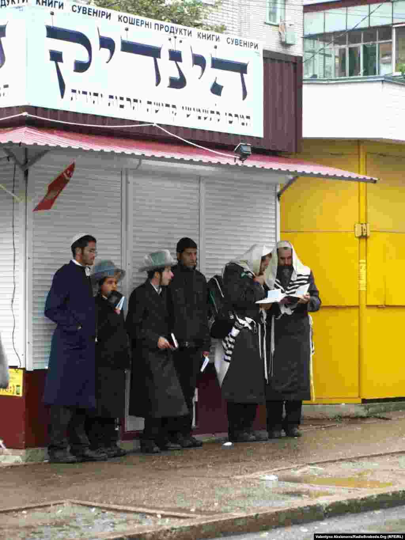 Злива не завадила охочим молитися та читати книги. Ці молоді хасиди сховалися під дах одного з багатьох уманських магазинів кошерних продуктів, які зачиняються на час шабату.