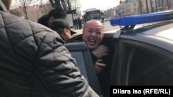 Полиция силой заталкивает активиста Мурата Аштаева в машину. Шымкент, 1 марта 2020 года.