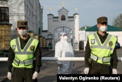 A Ukrainian health worker wearing protective gear stands next to members of the country's National Guard at the entrance to Kyiv's Pechersk Lavra monastery, where multiple cases of COVID-19 have been confirmed.
