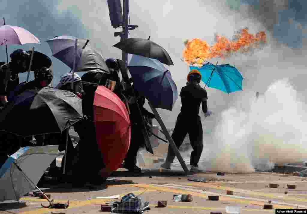 Парасолька протестувальника зайнялася під час сутичок із поліцією біля Гонконгського політехнічного університету, 17 листопада 2019 року