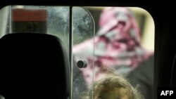 A young girl looks out from the back of an ambulance as it arrives in the port city of Misurata on April 17.