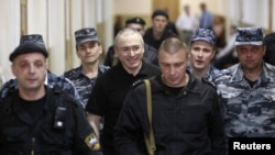 Mikhail Khodorkovsky (center, smiling) is escorted to court in Moscow in June 2011.