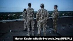 Медики-добровольці на даху дев'ятиповерхівки спостерігають за вечірнім боєм на території авдіївської промзони