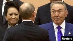 Президенты Нурсултан Назарбаев (справа) и Владимир Путин (стоит спиной) на саммите Совещания по взаимодействию и мерам доверия в Азии. Шанхай, 20 мая 2014 года.