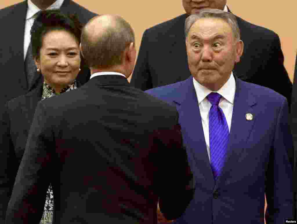 Kazakh President Nursultan Nazarbaev (right) reacts during a handshake with Russian President Vladimir Putin during a group photo for the fourth Conference on Interaction and Confidence Building Measures in Asia summit in Shanghai on May 20. (Reuters/Ng Han Guan/Pool)