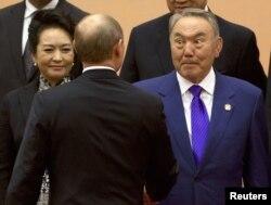 Президент Казахстана Нурсултан Назарбаев обменивается рукопожатием с президентом России Владимиром Путиным. Шанхай, 20 мая 2014 года.