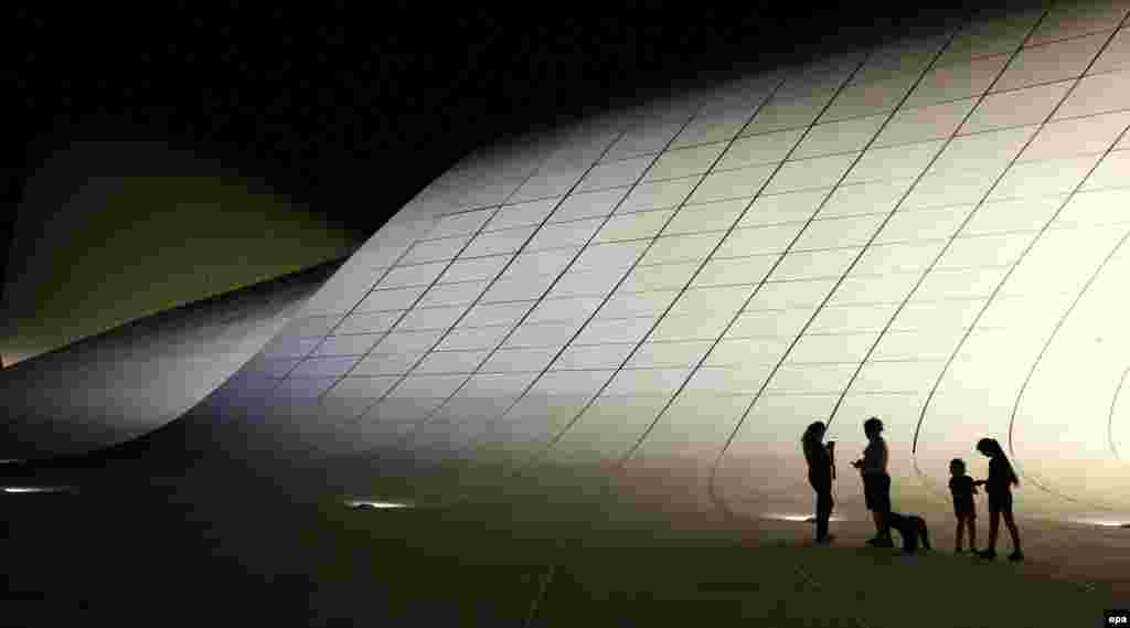 People stand in front the Heydar Aliyev Cultural Center in Baku, Azerbaijan. (epa/Zurab Kurtsikidze)