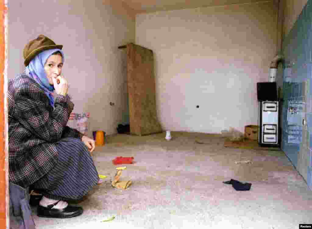A Bosnian Serb woman sits in her empty house as she prepares to leave the northern Bosnian town of Odzak on December 11, 1995. She was among 19,000 Bosnian Serbs that were relocated as the town came under Bosnian government control under the Dayton peace agreement.