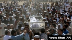 People carry the body of a victim of a toxic gas leak during his funeral prayer in Karachi on February 17.