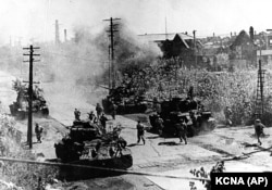 North Korean troops backed by Soviet-made tanks advance through Seoul in June 1950 a few days after the invasion began.