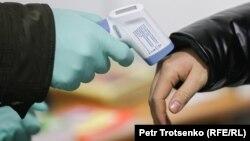 Работник супермаркета замеряет температуру тела посетителя. Иллюстративное фото.