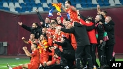 North Macedonian players celebrate after qualifying for their country's first major soccer tournament by beating Georgia in Tbilisi on November 12.