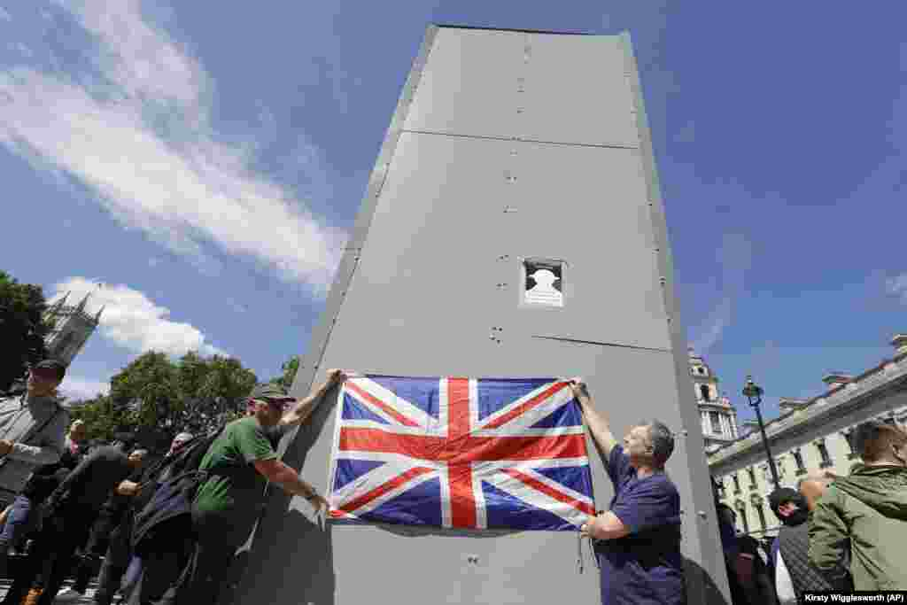 Members of far-right Football Lads Alliance hold a British flag in front of a protective covering surrounding the statue of former British Prime Minister Sir Winston Churchill in Parliament Square, central London, Saturday, June 13, 2020. British police have imposed strict restrictions on groups planning to protest in London Saturday in a bid to avoid violent clashes between protesters from the Black Lives Matter movement, as well as far-right groups.