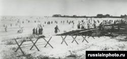 Большевики, некоторые в белых накидках для маскировки, прибывают к Кронштадту.