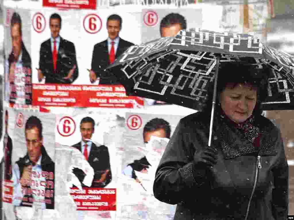 Caption: epa01212439 An elderly Georgian woman walks past electoral posters in Tbilisi, Georgia, 02 January 2008. Early presidential elections in Georgia are scheduled on 05 January 2008
