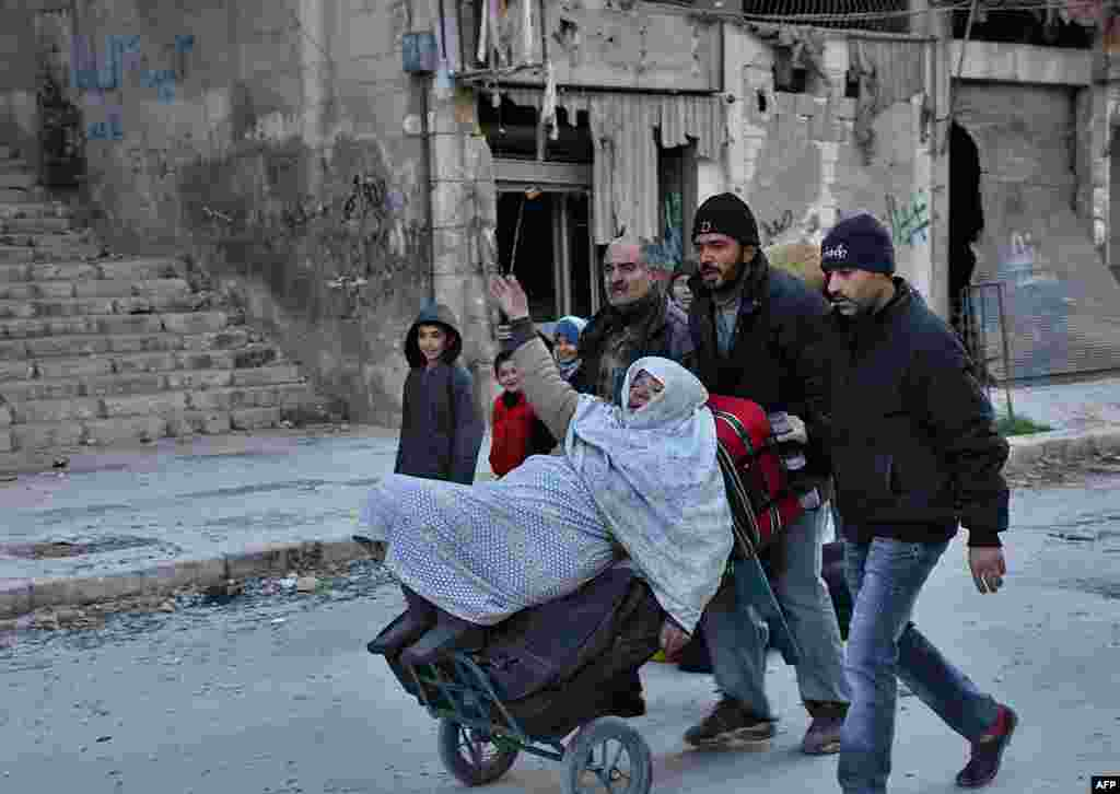 Syrian residents fleeing the violence in the eastern rebel-held parts of Aleppo evacuate from their neighborhoods through the Bab al-Hadid district after it was seized by the government forces on December 7. (AFP/George Ourfalian)