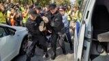 Полицейские задерживают участника акциии протеста в Алматы. 21 сентября 2019 года.