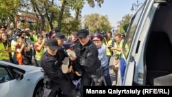 Сотрудники спецподразделения полиции несут задержанного к автозаку. Алматы, 21 сентября 2019 года.