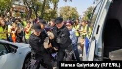 Сотрудники спецподразделения полиции несут задержанного к микроавтобусу. Алматы, 21 сентября 2019 года.